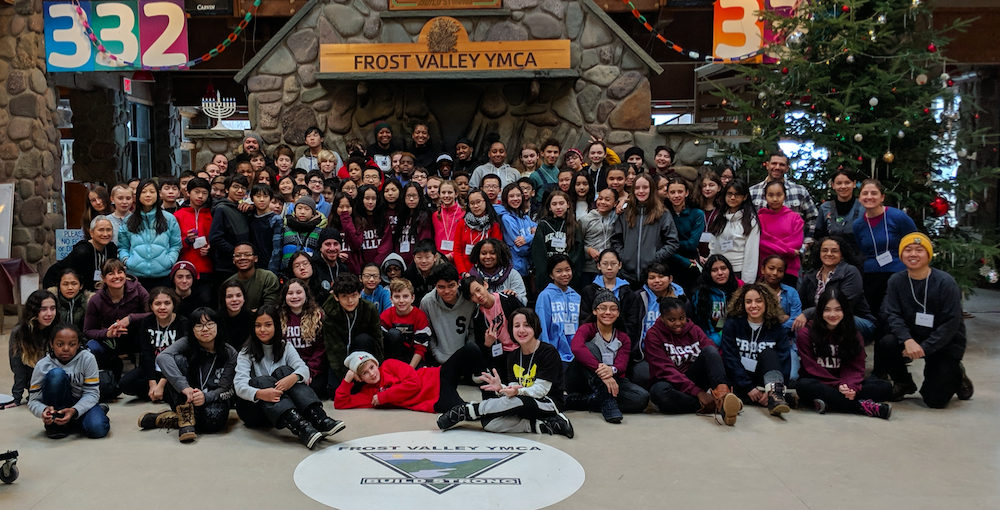 Group photo of students and staff in front of a fireplace at Frost Valley